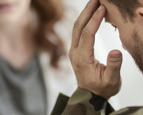 Close Up Of A Sad Soldier With Ptsd Talking About His Fears With A Psychiatrist Sitting In Blurred Background
